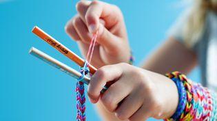 Un enfant fabrique un bracelet Rainbow Loom avec des élastiques à Munich (Allemagne), le 4 août 2014. (TOBIAS HASE / DPA / AFP)