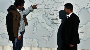 Deux migrants devant une carte de l'Europe à la frontière entre la Grèce et la Macédoine, le 22 février 2016. (SAKIS MITROLIDIS / AFP)