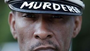"""Un homme porte une casquette de police sur laquelle est écrit """"meurtrier"""" à Ferguson (Missouri) aux Etats-Unis, le 17 août 2014. (CHARLIE RIEDEL / AP / SIPA)"""