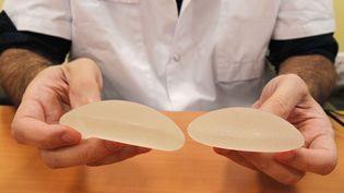 """Un médecin montre deux implants mammaires de type """"Poly Implant Prothèse"""" (PIP), le 21 décembre 2011 à Paris. (MICHEL EULER /AP / SIPA)"""