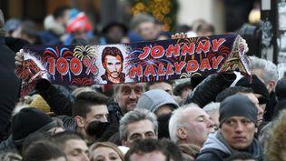 DECEMBRE. Des fans de Johnny Hallyday assistent à la cérémonie d'hommages organisée à Paris le 9 décembre. (BERTRAND GUAY / AFP)