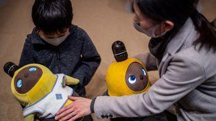 Des Japonais jouent avec le robot Lovot, à Kawasaki. (PHILIP FONG / AFP)