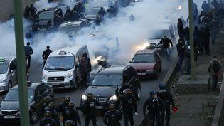 Des CRS interviennent contre les taxis grévistes, le 26 janvier 2016 près de la porte Maillot, à Paris. (THOMAS SAMSON / AFP)