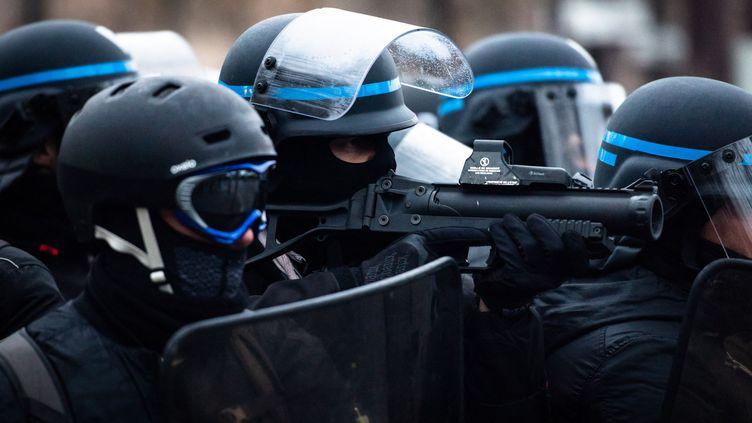 """Un policier avec unlanceur de balles de défense, le 12 janvier 2019 à Paris, lors d'une manifestation de """"gilets jaunes"""". (KARINE PIERRE / HANS LUCAS / AFP)"""