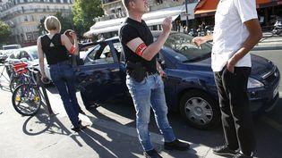 """Des policiers de la brigades des """"Boers"""", la police des taxis, contrôlentun chauffeur Uber, le 29 juin 2015 à Paris. (THOMAS SAMSON / AFP)"""
