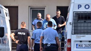 La police escorte Gheorghe Dinca, suspecté du meurtre d'une adolescente à Craiova, en Roumanie, le 30 juillet 2019. (BOGDAN DANESCU / AFP)