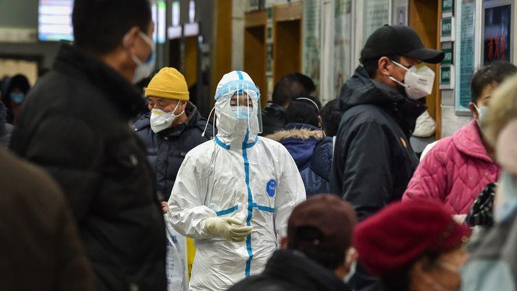 Des habitants de Wuhan portent des masques pour se protéger d'une contamination, le 24 janvier 2020. (HECTOR RETAMAL / AFP)