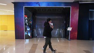 Un couple marche devant le cinéma Megabox fermé à Pékin, en Chine, le 16 février 2020. L'établissement aux huit écrans est fermé depuis près d'un mois à cause de la crise du coronavirus. (GREG BAKER / AFP)