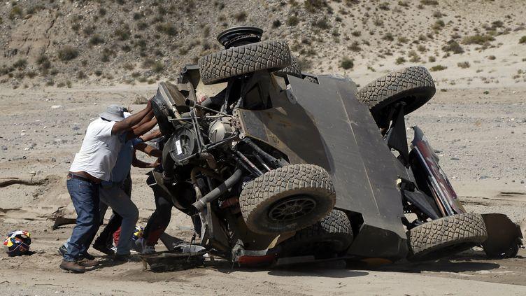 Sébastien Loeb et son copilote Daniel Elena tentent de remettre leur véhicule à l'endroit après un accident, le 11 janvier 2016, en Argentine. (DPPI / DPPI MEDIA)