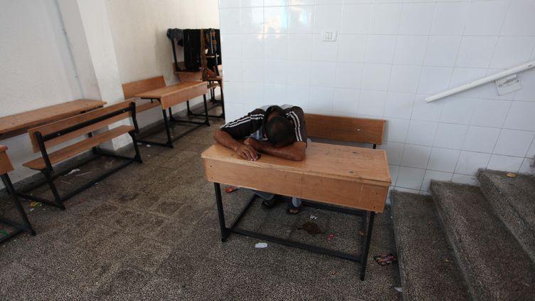 Un Palestinien se repose dans une école de l'ONU, à Gaza City, le 23 juillet 2014. (ASHRAF AMRA / ANADOLU AGENCY / AFP)