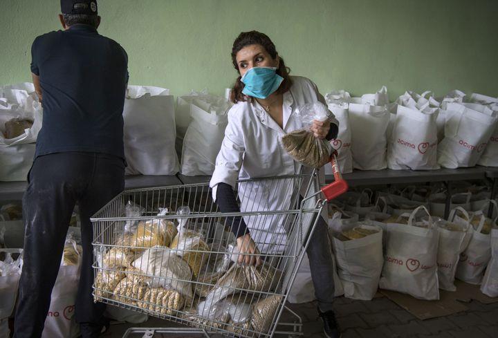 Des bénévoles de l'association Insaf préparent des colis à Casabanca, le 8 avril 2020. (FADEL SENNA / AFP)