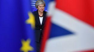 Theresa May, Premier ministre britannique vue à travers des drapeaux européen et britannique, à Bruxelles (Belgique). (EMMANUEL DUNAND / AFP)