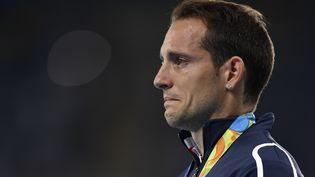 Vice-champion olympique, le perchiste français Renaud Lavillenie est ému aux larmes après avoir été hué durant la cérémonie de remise des médailles, mardi 16 août, lors des Jeux olympiques de Rio (Brésil). (FABRICE COFFRINI / AFP)