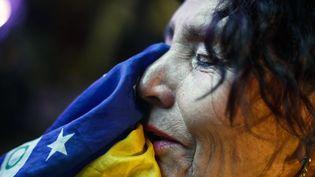 Une supportrice brésilienne dévastée par l'élimination de son pays en demi-finale de la Coupe du monde par l'Allemagne, le 8 juillet 2014, à Sao Paulo (Brésil). (MIGUEL SHINCARIOL / AFP)