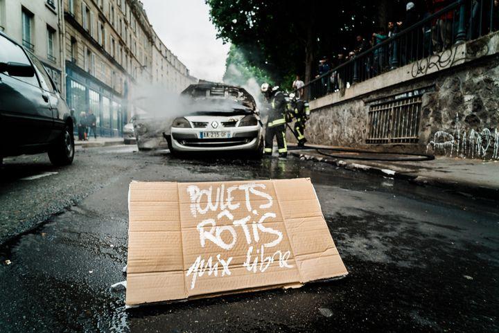 Un écriteau déposé devant la voiture de police incendiée, le 18 mai 2016 à Paris. (SIMON GUILLEMIN / HANS LUCAS / AFP)