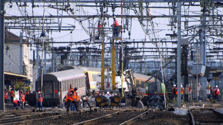 Secouristes et enquêteurs s'affairent après le déraillement d'un trainParis-Limoges en gare de Brétigny-sur-Orge (Essonne), qui a fait sept morts et 26 blessés, le 12 juillet 2013. (ETIENNE LAURENT / MAXPPP)