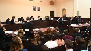 Salah Abdeslam, en veste blanche et de dos au premier rang, et son complice présume Sofiane Ayari, en gris et debout à sa droite, s'assoient dans la salle d'audience du palais de justice de Bruxelles au premier jour de leur procès, le 5 février 2018. (EMMANUEL DUNAND / AFP)