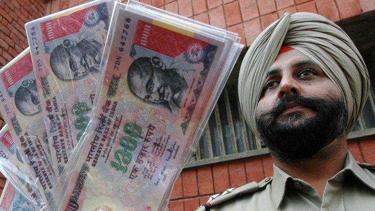 Un fonctionnaire de police indien avec des liasses de faux billets de 1000 roupies. ( AFP PHOTO / NARINDER NANU)