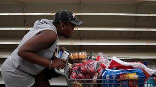 Une femme passe devant des rayons vides dans un supermarché de Miami Beach, en Floride (Etats-Unis), le 7 septembre 2017. (CARLO ALLEGRI / REUTERS)