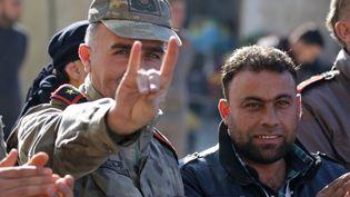 Un homme vêtu d'un uniforme d'officier turc fait le signe des Loups gris lors d'une manifestation de soutien à la Turquie voisine, dans la ville syrienne de Bizaa,le 21 décembre 2018. (BAKR ALKASEM / AFP)