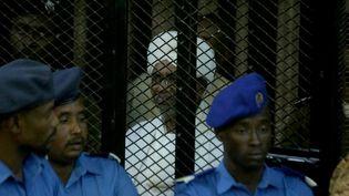 Au centre, en blanc, l'ancien président soudanais Omar el-Béchir lors de son procès pour corruption à Khartoum, la capitale du Soudan, le 14 décembre 2019. (MAHMOUD HAJAJ / ANADOLU AGENCY)