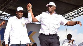 Amadou Gon Coulibaly (à gauche), alors Premier ministre, tient la main d'Hamed Bakayoko (à droite), alors ministre de l'Intérieur et candidat à la municipalité d'Abobo, un quartier d'Abidjan (la capitale économique de la Côte d'Ivoire), lors du démarrage de la campagne pour les élections régionales et municipales le 29 septembre 2018. (ISSOUF SANOGO / AFP)