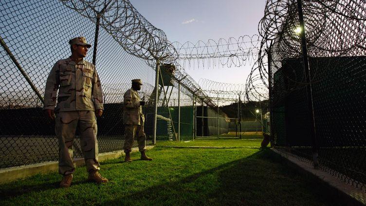 Des soldats américains se tiennent devant un camp de détenus chinois, le 28 octobre 2009, au centre de détention américain de Guantanamo, à Cuba. (JOHN MOORE / GETTY IMAGES NORTH AMERICA / AFP)