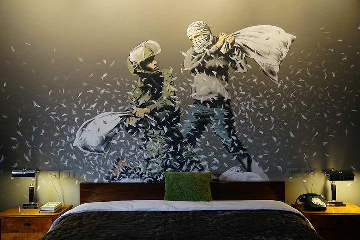 """Au dessus du lit de la chambre """"Artist"""" du Walled Off hotel à Bethléem, une oeuvre de Banksy.  (http://walledoffhotel.com/)"""