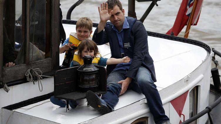 Brendan Cox, le veuf de la députée britannique assassinée Jo Cox, et leurs deux enfants font le chemin sur un bateau, sur la Tamise, près de Londres, le 22 juin 2016. (ALASTAIR GRANT / AP / SIPA)