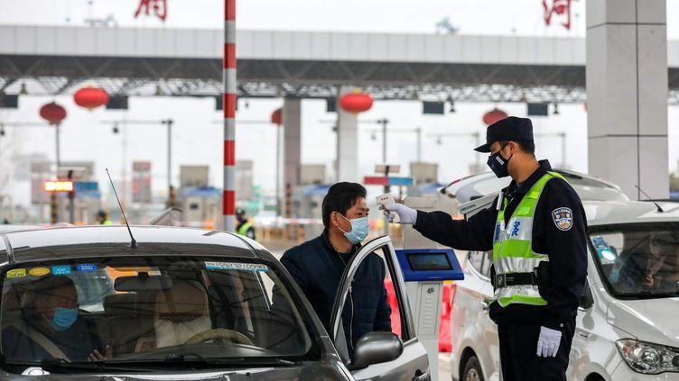 Un policier contrôle la température d'un automobiliste au niveau d'un péage de Wuhan, en Chine, jeudi 23 janvier 2020. (MAXPPP)