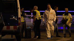 Les enquêteurs sur la zone où un véhicule a foncé sur la foule, à Cambrils (Espagne), jeudi 17 août 2017, avant de se retourner. (LLUIS GENE / AFP)