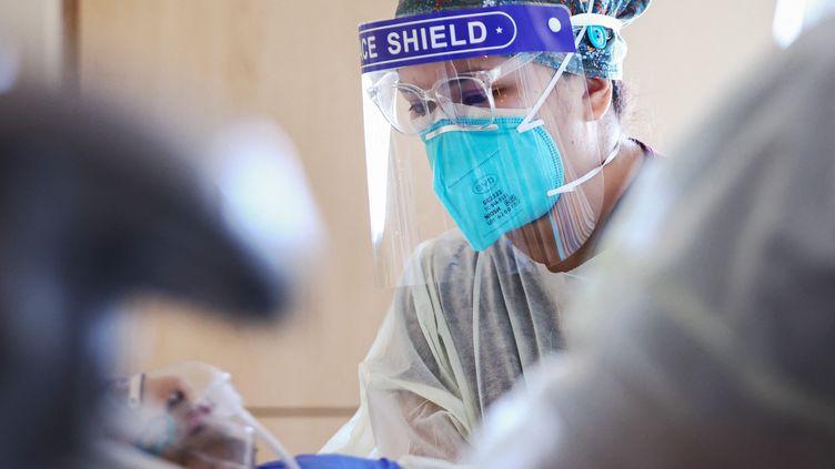 Une infirmière prend en charge un patient positif au Covid-19, le 30 juillet 2021 à Los Angeles, en Californie. (MARIO TAMA / GETTY IMAGES NORTH AMERICA / AFP)