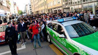 Des réfugiés arrivés en train à Munich sont escortés vers des hébergements, le 12 septembre 2012. (SVEN HOPPE / DPA / AFP)