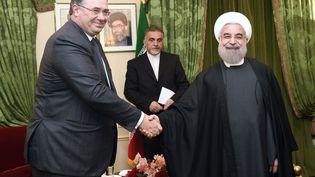Le PDG de Total, Patrick Pouyanné, serre la main du président iranien Hassan Rohani, le 28 janvier 2016 à Paris. (ERIC FEFERBERG / AFP)