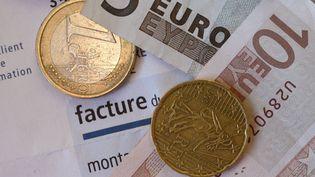 Des billets et des pièces de monnaie sur une facture EDF. (DAMIEN MEYER / AFP)