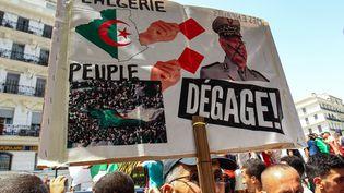 Un manifestant algérien brandit une pancarte sur laquelle on inflige auchef de l'armée, Ahmed Gaïd Salah, un carton rouge (exclusion au football), à Alger, le 12 juillet 2019. (- / AFP)