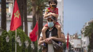 Un père avec son fils sur les épaules dans le centre de Rabat, la capitale du Maroc, le 16 juin 2020. (FADEL SENNA / AFP)