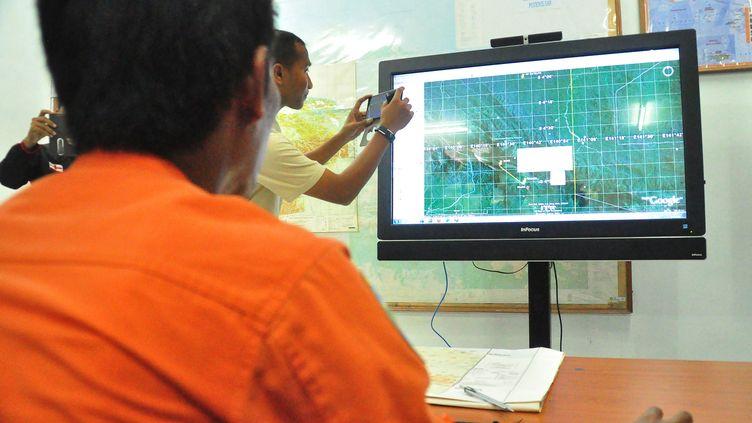 A Jayapura (Indonésie), des membres des équipes de secours et de recherche indonésiennes regardent une carte de la zone où un avion de ligne a disparu le 16 août 2015. (INDRAYADI / AFP)