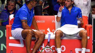 Yannick Noah et Lucas Pouille (à droite) en grande discussion lors du premier match de la finale de la Coupe Davis face à la Belgique, le 24 novembre 2017 à Villeneuve-d'Ascq (Nord). (PHILIPPE HUGUEN / AFP)