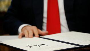Donald Trump signe le décret qui met fin à la séparation des familles de migrants à la frontière entre les Etats-Unis et le Mexique, le 20 juin 2018. (YURI GRIPAS / REUTERS)
