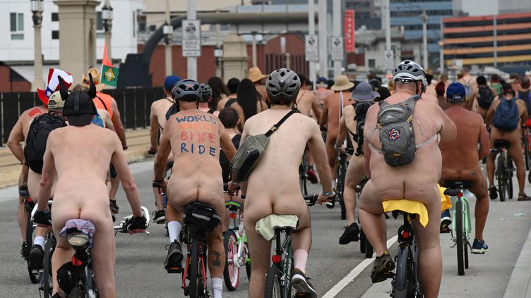 Riders in various states of undress participate in the World Naked Bike Ride in Los Angeles, California on June 22, 2019. - The worldwide event aims to promote bicycles and other non-fossil fuel burning vehicles for transportation, as well as promote body positive values. (Photo by Robyn Beck / AFP) (ROBYN BECK / AFP)
