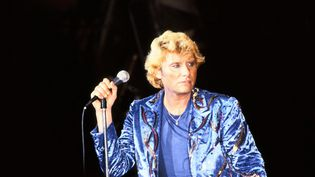 Les vêtements bleus et la crinière blonde, Johnny chante devant son public à Paris, le 15 septembre 1982. (KEYSTONE-FRANCE / GAMMA-KEYSTONE / GETTY IMAGES)