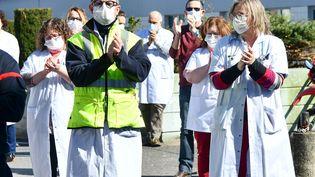 Des membres du personnel soignant de l'hôpital de Compiègne (Oise) participent à un hommage en l'honneur deJean-Jacques Razafindranazy, médecin décédé des suites du coronavirus, le 23 mars 2020. (RICHARD DUGOVIC / AFP)