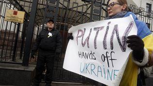 """Une manifestante brandit une pancarte indiquant """"Poutine, ôte tes mains de l'Ukraine"""", devant l'ambassade russe à Kiev, le 1er mars 2014. (YURY KIRNICHNY / AFP)"""