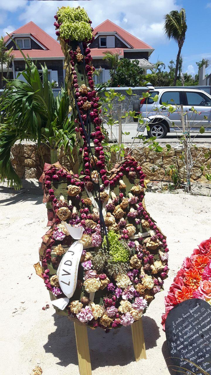 Une gerbe en forme de guitare près de la tombe de Johnny Hallyday à Saint-Barthélemy. (JÉRÔME VAL / RADIO FRANCE)