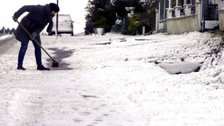 Une habitant de Longueville, en Ile-de-France, déneigela route après le passage de la tempête Egon, le 13 janvier 2017. (MAXPPP)