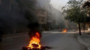 De la fumée s'échappe de pneus incendiés dans une rue d'Alep (Syrie) par des rebelles, dimanche 31 juillet 2016, afin de lutter contre les frappes aériennes pro-gouvernementales. (BEHA EL HALEBI / ANADOLU AGENCY / AFP)