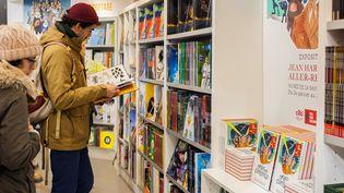 Un visiteur du Festival d'Angoulême 2019 lit une BD. (YOHAN BONNET / AFP)