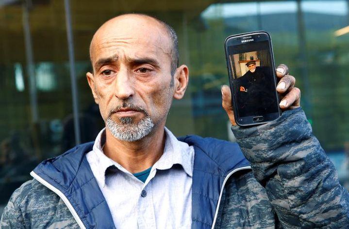 Omar Nabi montre une photo de son père, Haji Daoud, devant le tribunal de Christchurch, le 16 mars 2019. Son père est l'une des victimes de la tuerie perpétrée parBrenton Tarrant la veille dans deux mosquées decette petite commune néo-zélandaise. (REUTERS)