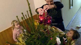 Décoration d'un sapin de Noël par une famille à Sant-André-sur-Orne, le 7 décembre 2003. (MYCHELE DANIAU / AFP)